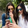 This shows two women looking at a smart phone
