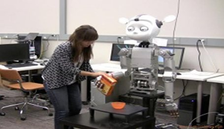 A woman is holding the hand of a robot as it appears to pour something from a box into a bowl on a table. The robot's eyes appear to be half open.