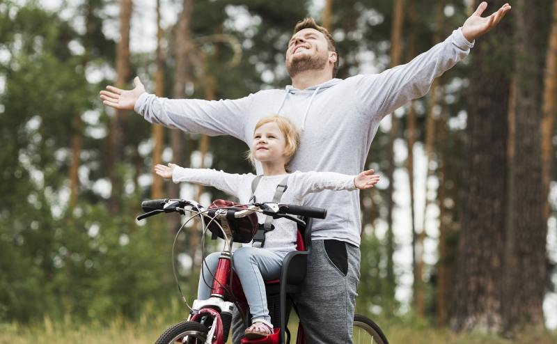 Father and daughter riding on bicycle