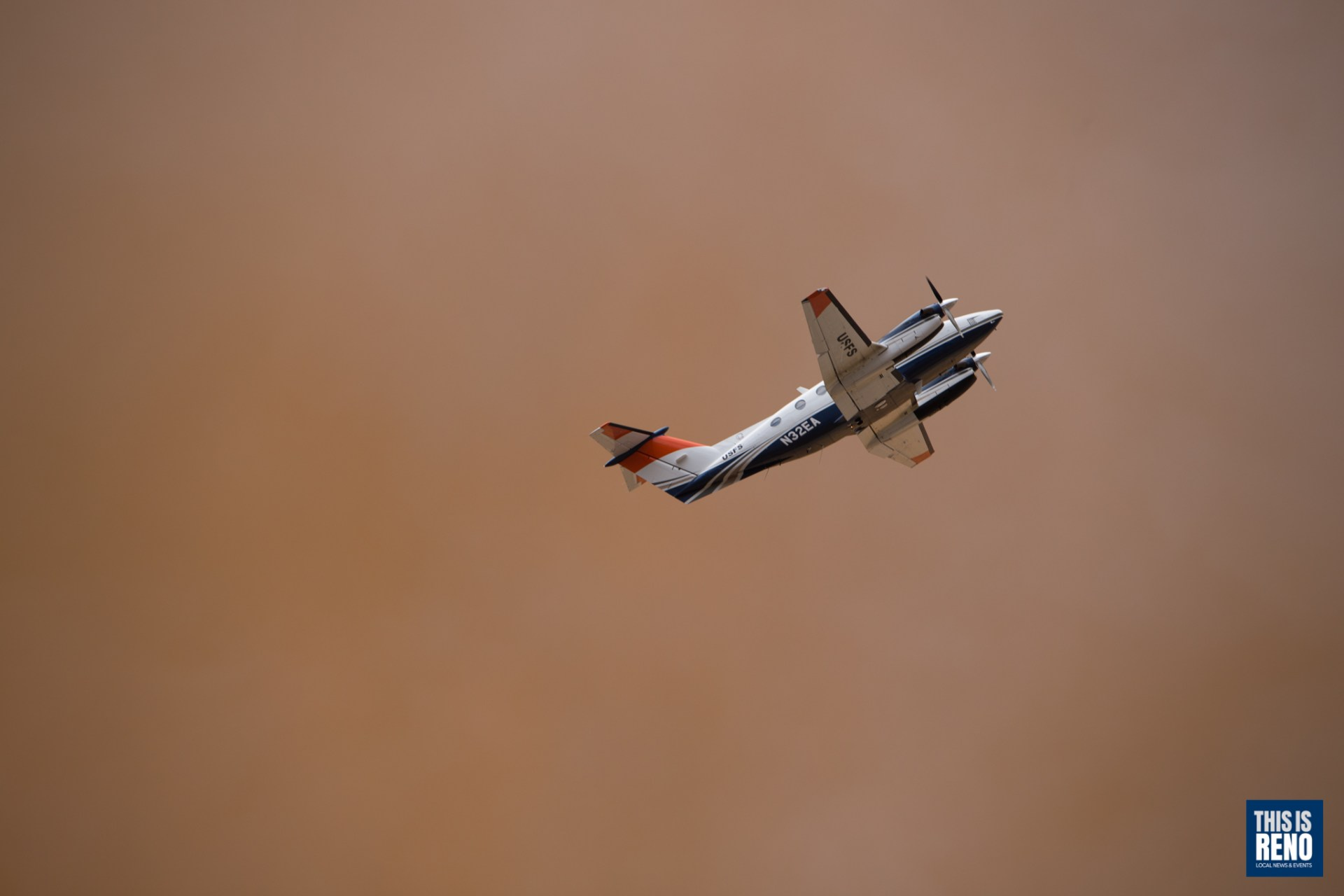 A US Forest Service air attack plane flies over a wildfire to coordinate air resources.