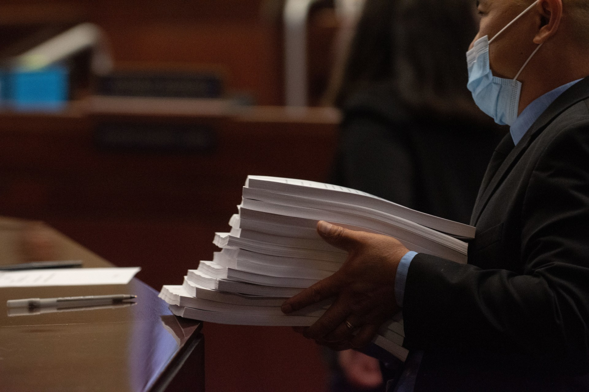 A Nevada Assembly Sergeant at Arms passes out a bill draft request during a recess on the second day of the 31st Special Session of the Nevada Legislature in Carson City, Nev., on Thursday, July 9, 2020. (David Calvert/The Nevada Independent)