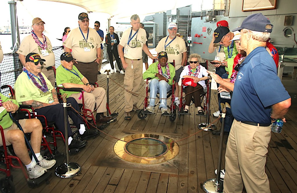 A tour guide aboard the USS Missouri shows Honor Flight Nevada World War II veterans and their handles the exact spot where the Instrument of Surrender was signed.
