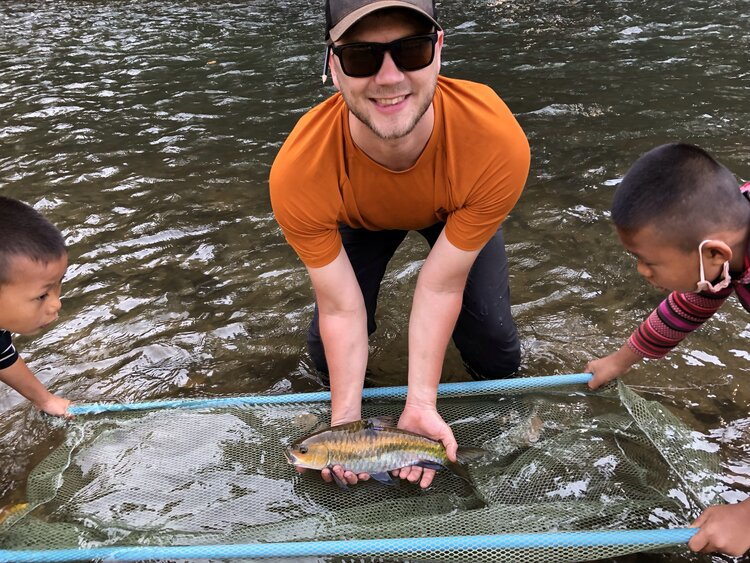 Fieldwork in communities often results in curious onlookers, presenting a great opportunity for inclusion and awareness raising. Here two regular observers help Aaron Koning release a radio-tagged mahseer as part of his research on fish movement in Mae Ngao, Mae Hong Son, Thailand.