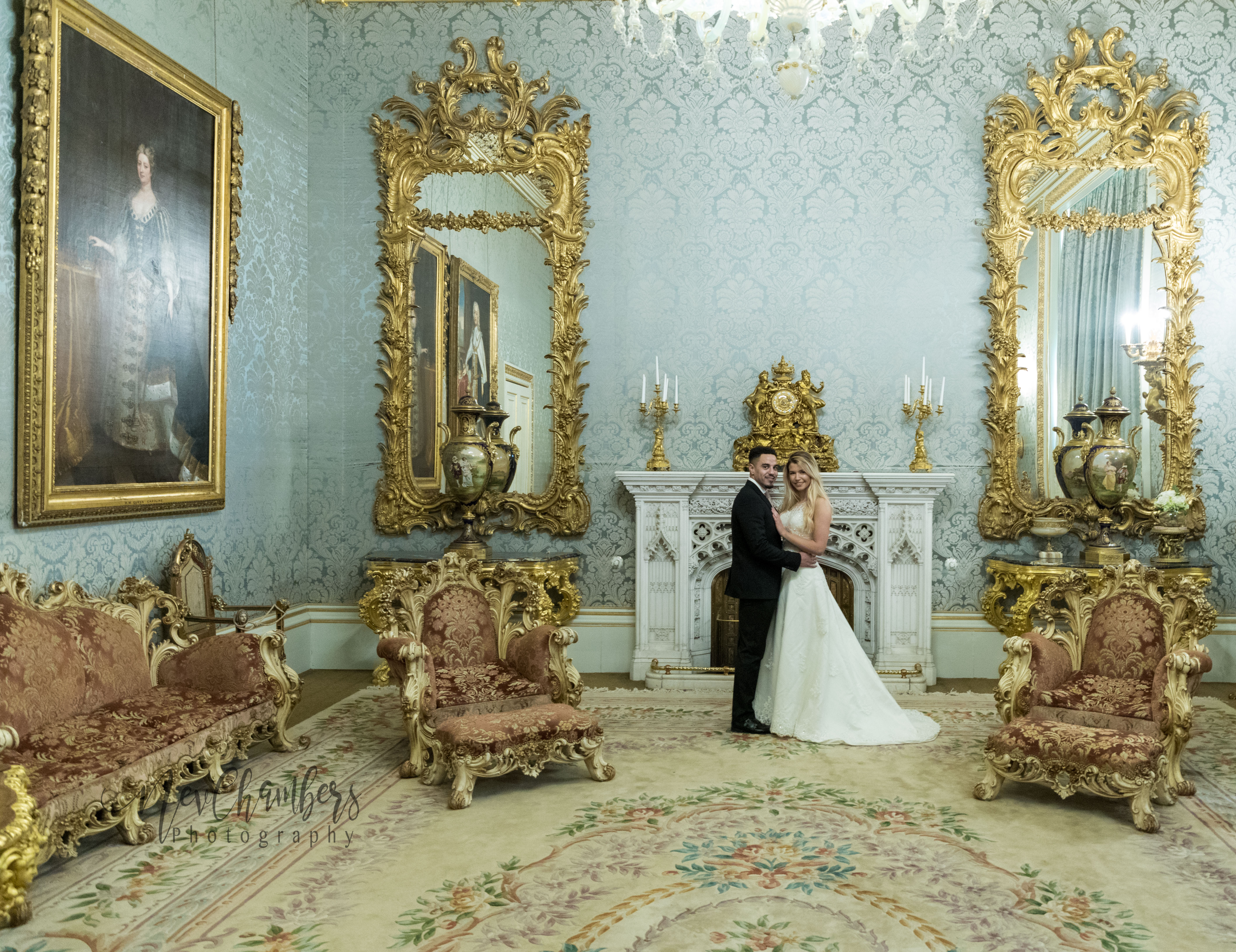bride and groom pose in front of ornate fireplace. Large gold clock in the centre of fireplace. Either side there are two extremely large gold mirrors.