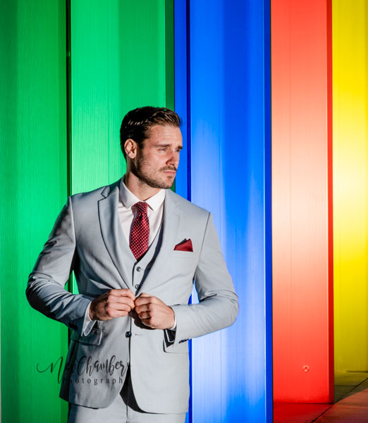Groom posing next to wall which photographer has lit with green, red, blue and yellow lights. Groom shown at his very best