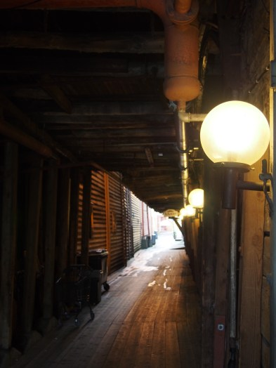 Dimly-lit walkways between the closely-packed warehouses.