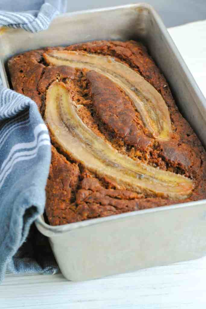 healthier whole wheat banana bread in baking pan with gray cloth with white stripes