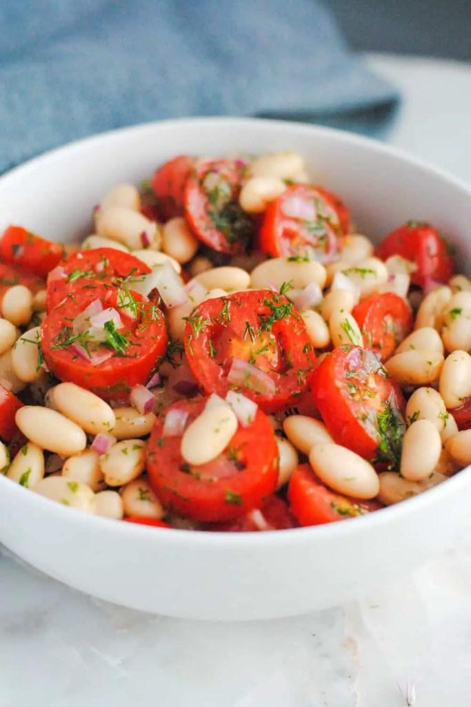 white bowl of white bean tomato and dill salad