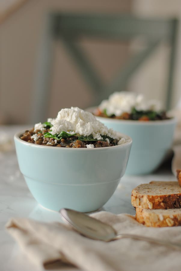 Two bowls of lentils with goat cheese and spinach served with bread