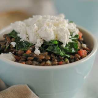 A bowl of lentils topped with goat cheese and spinach