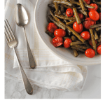 balsamic roasted green beans and tomatoes in serving dish with serving utensils
