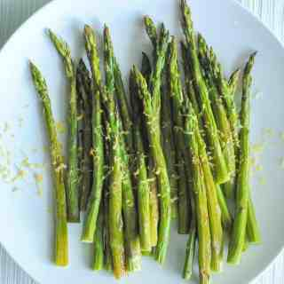 roasted asparagus on white plate with lemon zest