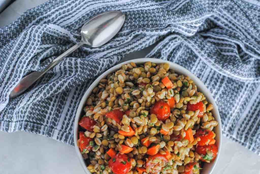 lentil salad in white bowl next to gray cloth