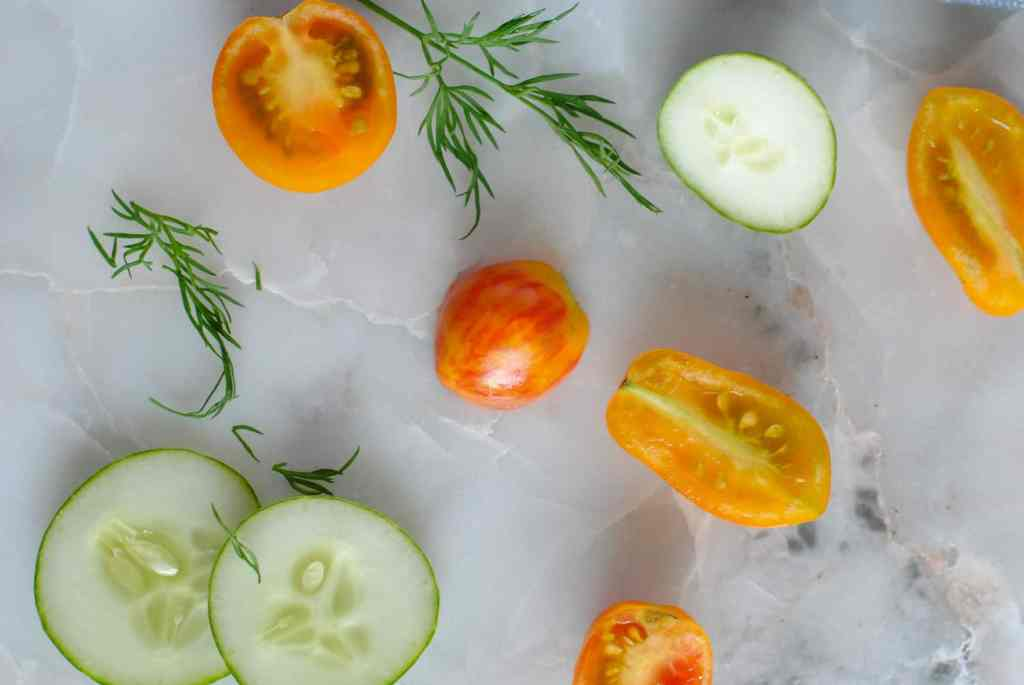 tomatoes cucumbers and dill on marble background