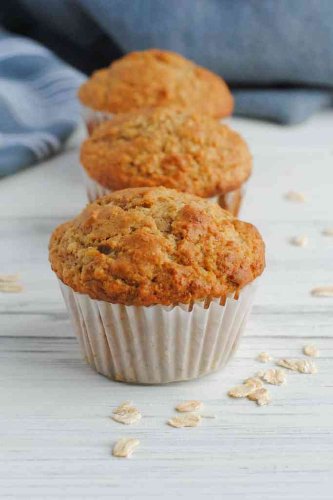 three muffins on white background with oats