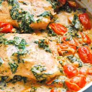skillet with salmon in a creamy garlic, spinach and tomato sauce