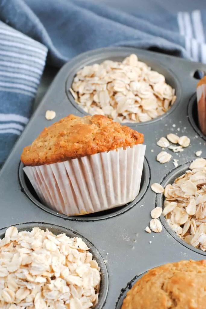 cinnamon oatmeal muffin and oats in muffin tin