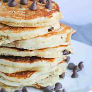 stack of buttermilk pancakes topped with chocolate chips on white plate