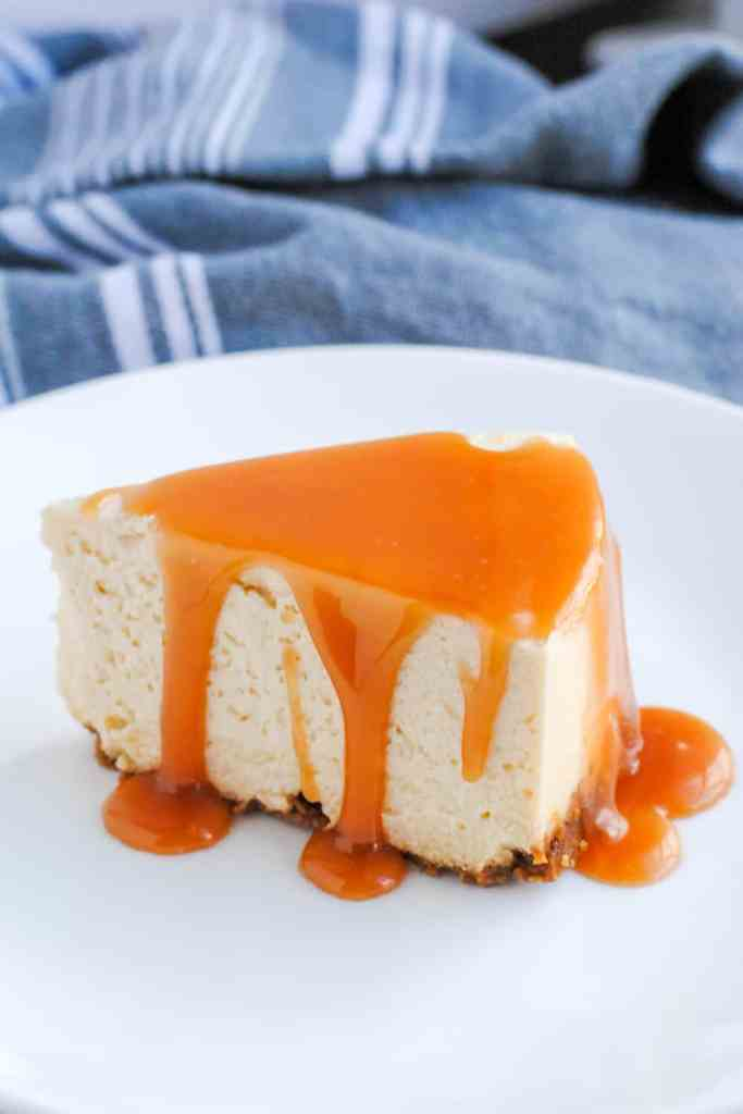 slice of cheesecake with salted caramel sauce drizzled on top set on a white plate with gray background