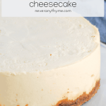 cheesecake on a white plate with gray and white striped towel in background with text overlay instant pot cheesecake neveranythyme.com