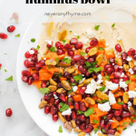 hummus topped with pomegranates, sweet potato, feta cheese, pistachios, fresh chopped parsley and mint with words nourishing hummus bowl neveranythyme.com