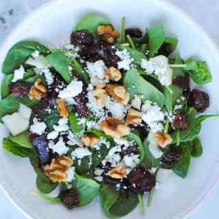bowl of spinach leaves topped with roasted beets, pears, dried cherries, goat cheese, walnuts