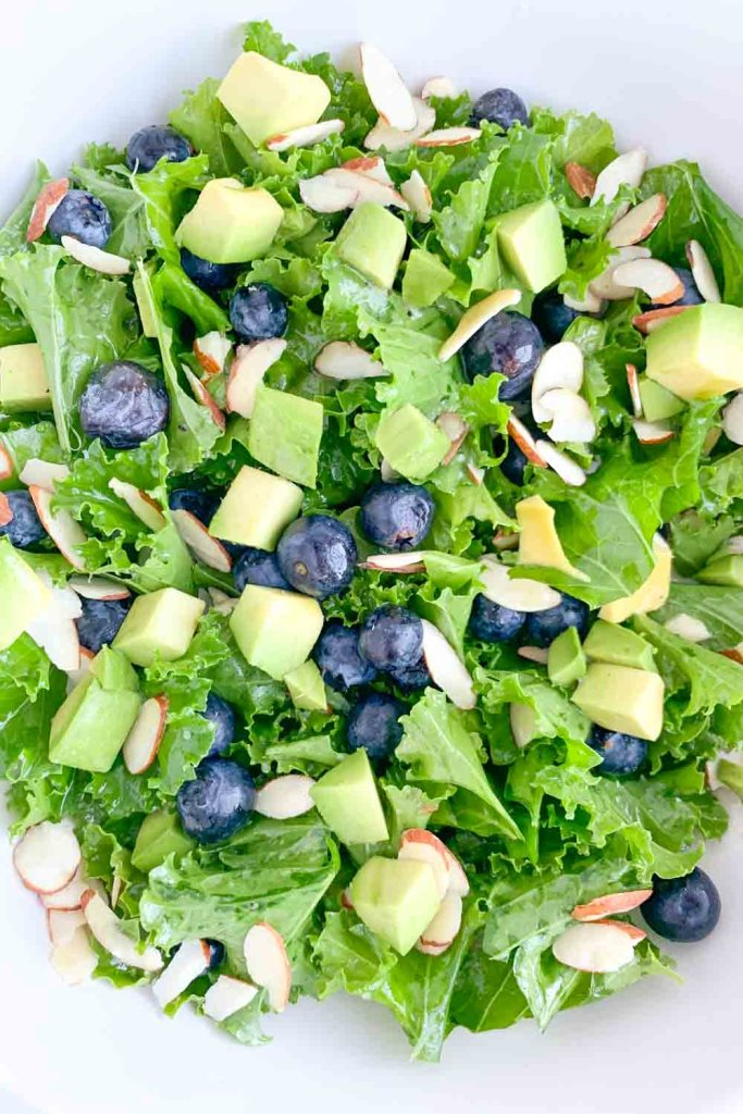 white bowl with kale salad topped with blueberries, avocado, sliced almonds and honey lime vinaigrette dressing