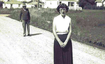 Woman standing in road, man photobombing her