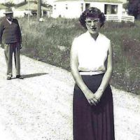 Woman standing in road, man photobombing her