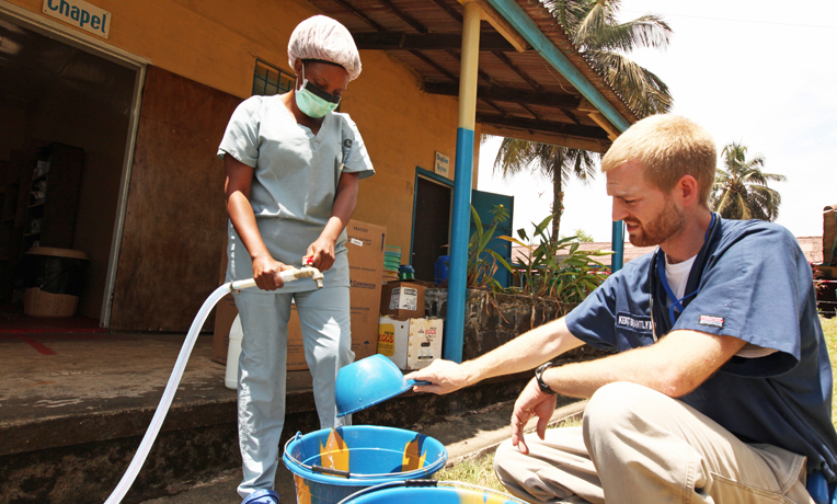 Dr. Brantly makes chlorine solution for disinfection at the case management center at ELWA Hospital.