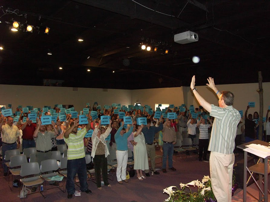 "Higher Calling congregation raise signs reading ""Never Settle"""