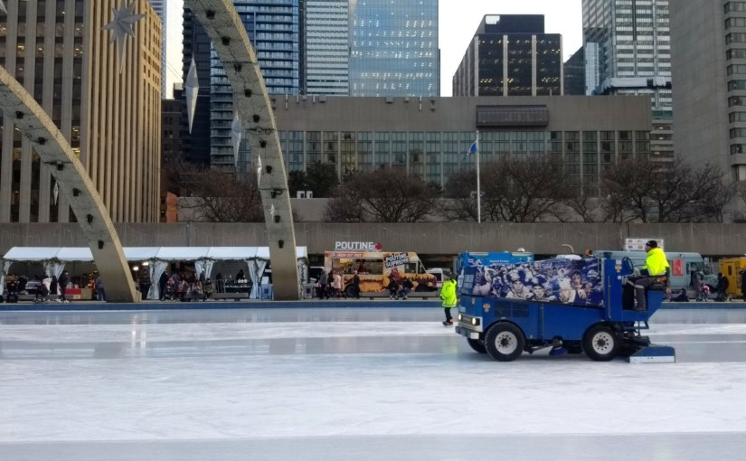 At the Nathan Phillips Square skating rink, a zamboni slowly rolls by with a poutine truck in the background.