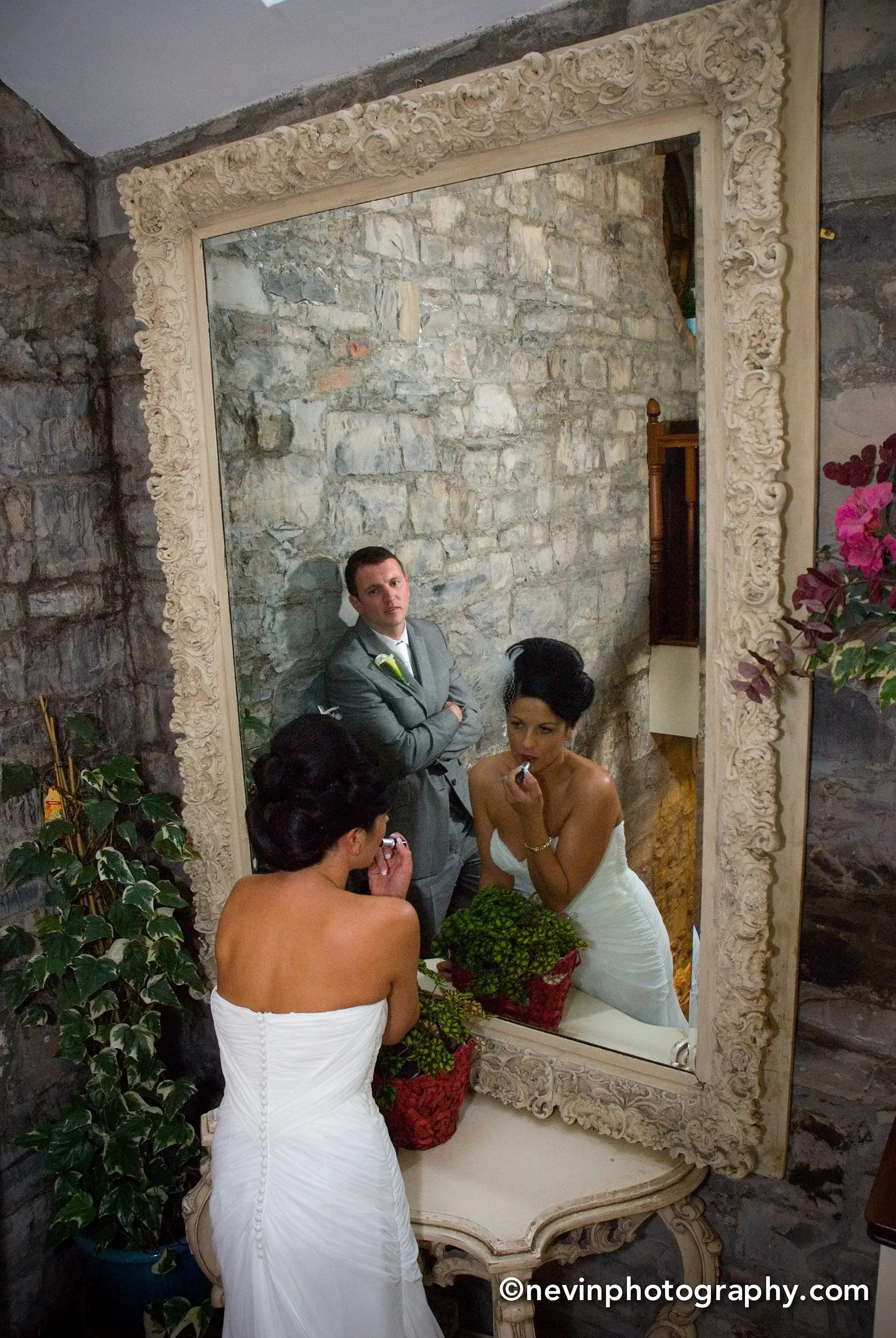 Bride doing final touch ups before meeting her guests- with husband patiently waiting