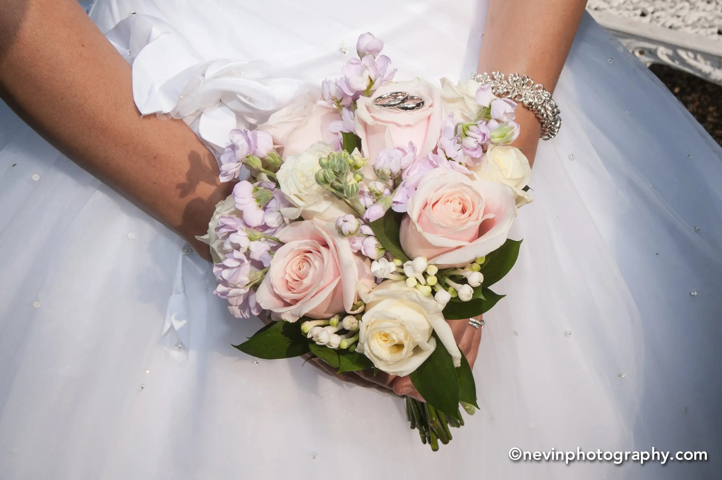 Close up of brides hands holding her flower bouquet with wedding rings on top