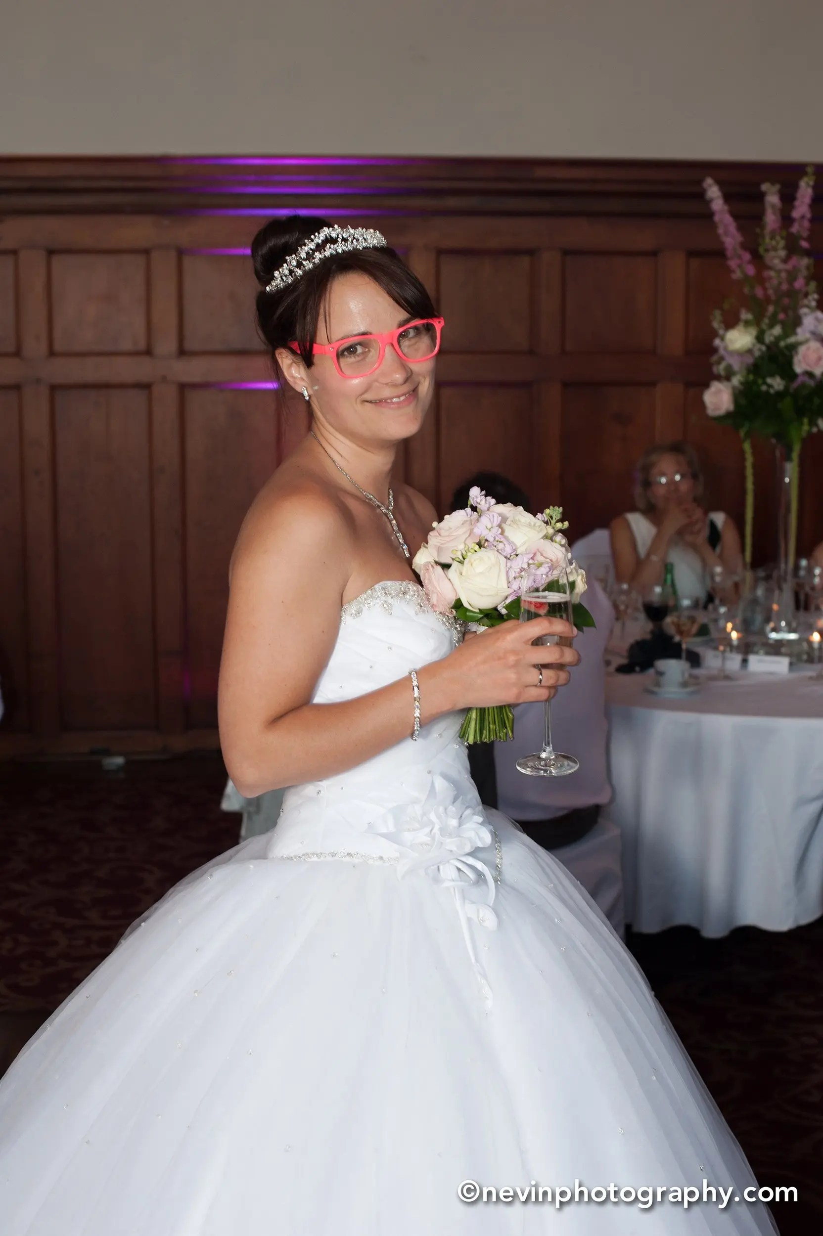 Bride smiling holding her champagne and bouquet while wearing funky glasses