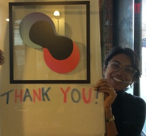 """Isha holding up a sign that says """"thank you"""""""