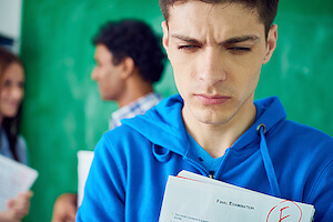 Frustrated student holding exam paper with bad mark