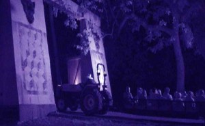 A tractor pulls victims through the gate leading to haunted territory