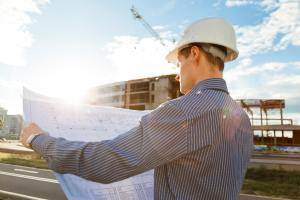 Architect in helmet with blueprints looks at camera in a building site