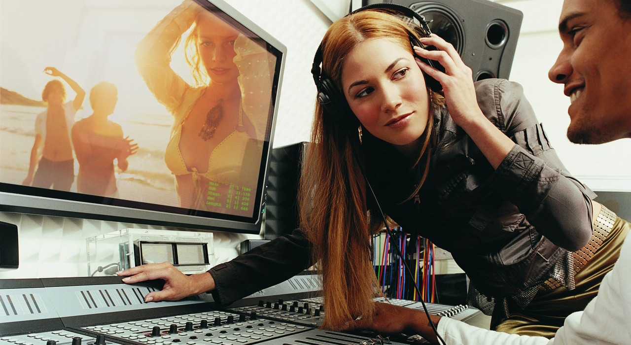Pop Musician Listening to Music on Her Headphones in a Recording Studio as a Producer Watches a Video on a Plasma Screen --- Image by © 2/Ocean/Corbis