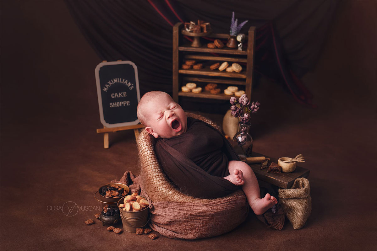Olga Vuscan New Born Photographer for Workshops by Camen Bergmann Studio new born baby yawns in a library-like background