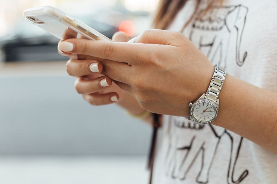 Woman wearing white holding her phone