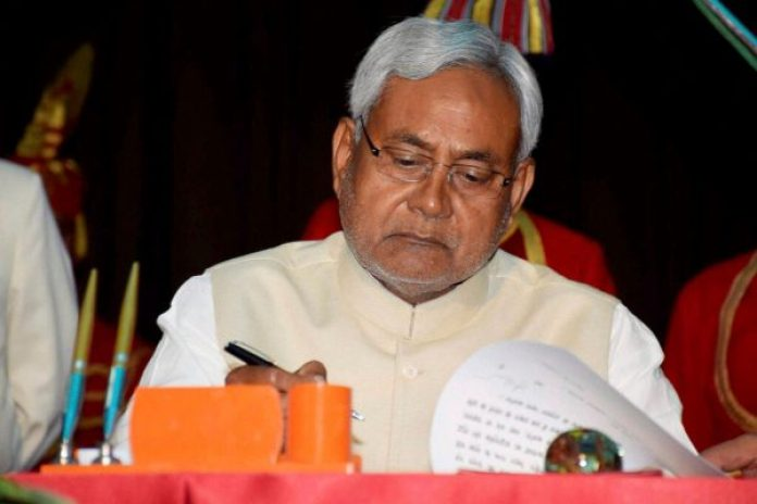 Patna: JD(U) strongman and former chief minister of Bihar Nitish Kumar signs official documents after taking oath as state's CM for the fourth from Bihar Governor Keshari Nath Tripathi at Raj Bhawan in Patna on Sunday. PTI Photo (PTI2_22_2015_000122B)