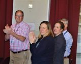 Rob Taylor, Chief of Health Administration; Nancy Short, Executive Assistant to the Director; and Greer Sullivan, Executive Assistant to the Nurse Executive, giving the Veterans a standing ovation.