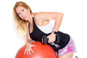 Female personal trainer in Northampton holding a dumbbell.