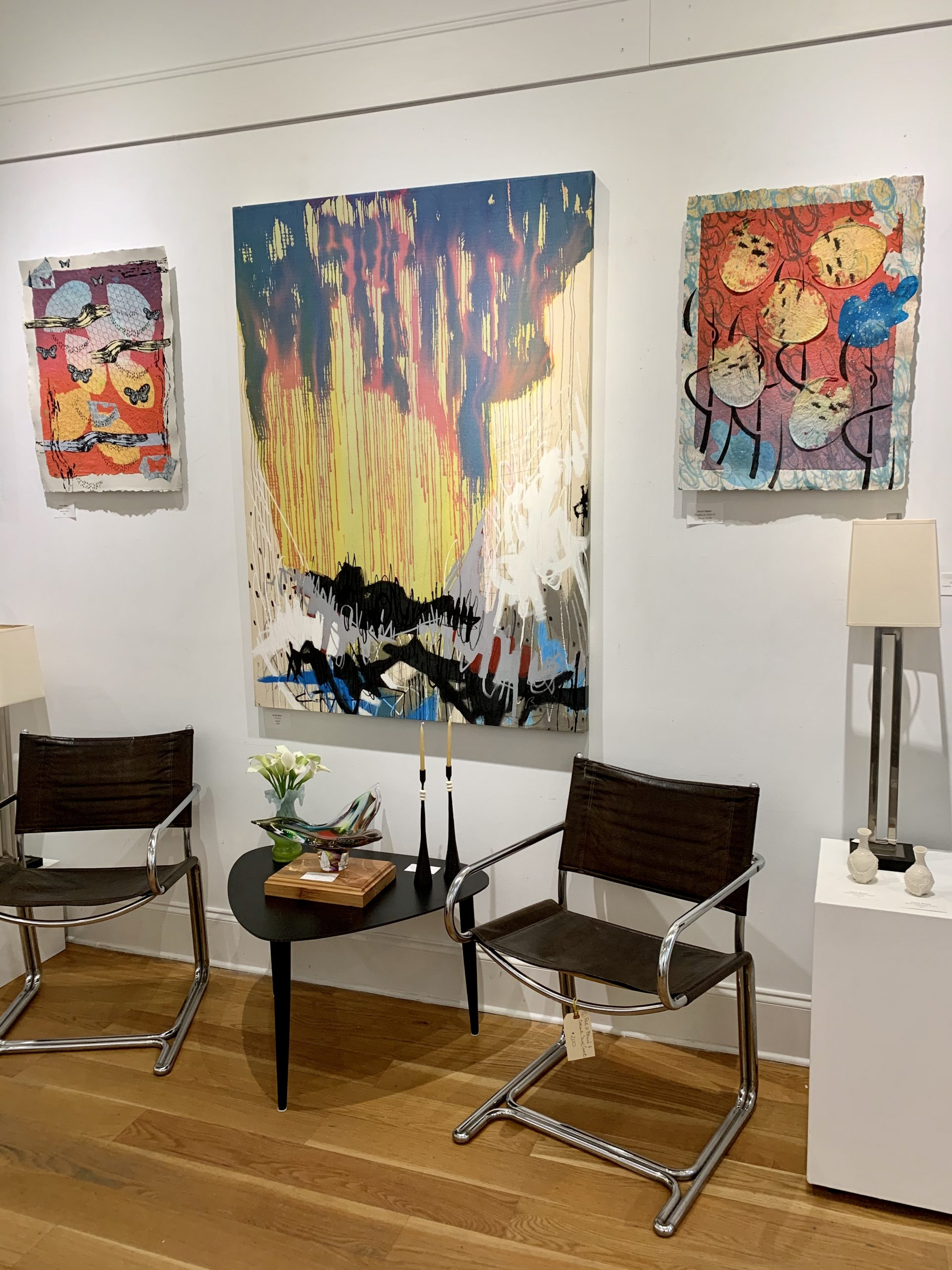 """The red in all these pieces make an arc and make them relate to one another. """"Fireflies at Dawn I and II"""" by Fritzi Huber and in the middle an abstract by Kevin Bass. Furniture by Decades of Decor."""