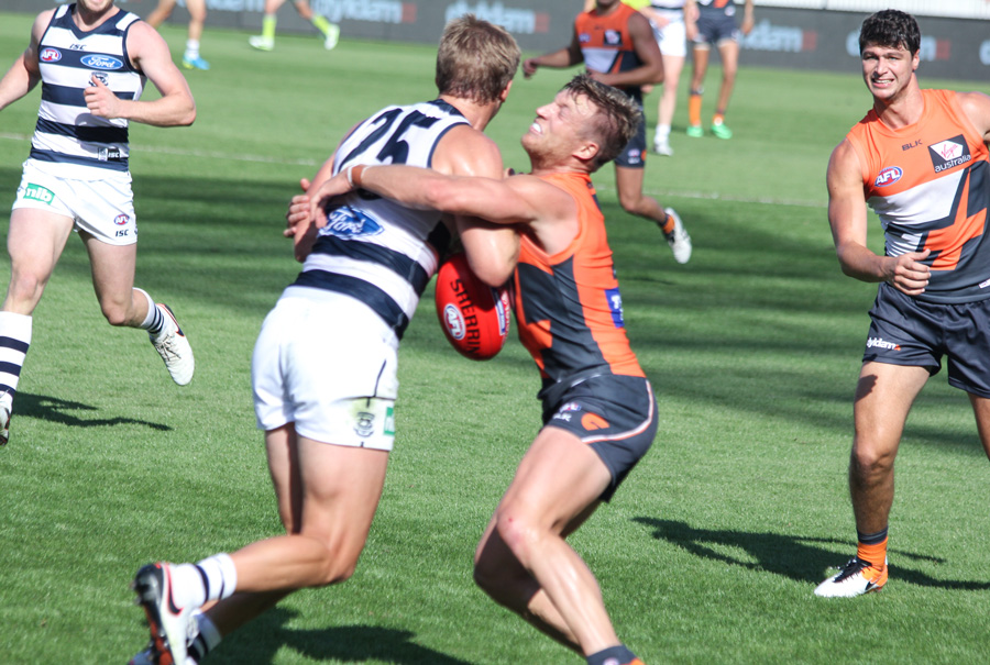 Rhys Palmer of the GWS Giants lays a solid tackle on Geelong's Lachie Henderson