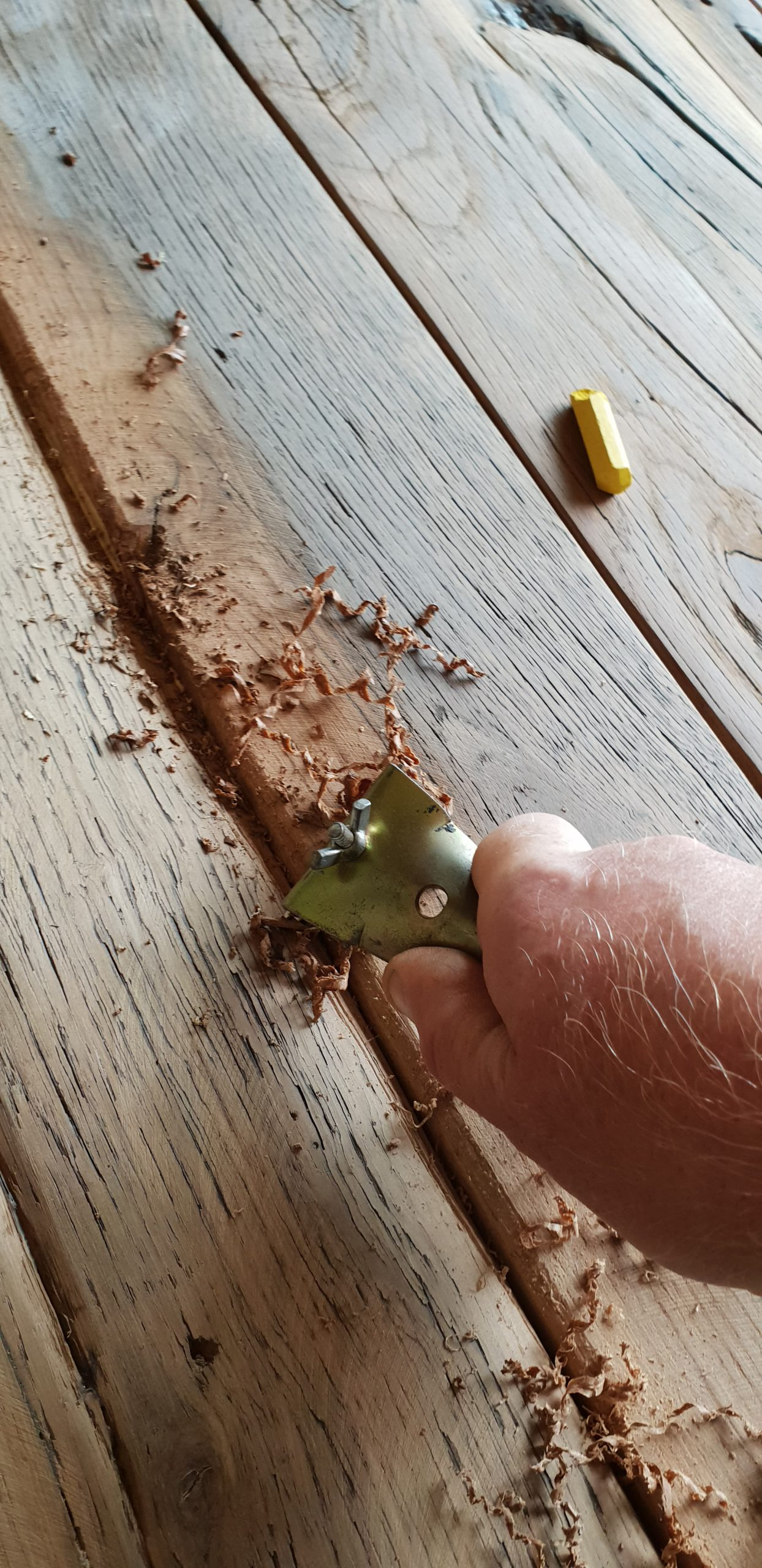 hand scraping a reclaimed oak floor before sanding