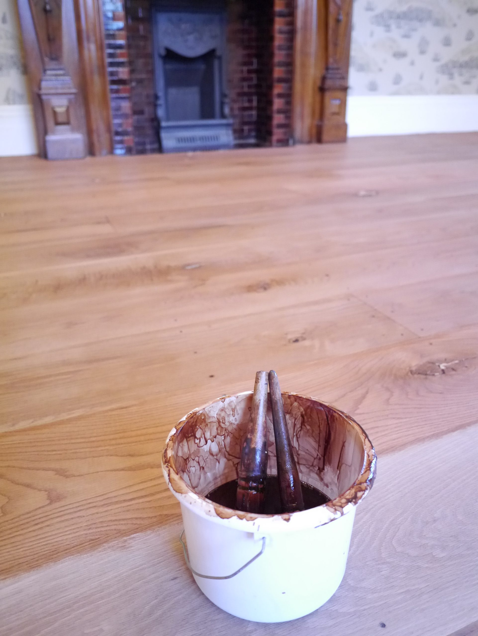 Cloe up of coating pot and brush whilst staining oak floor