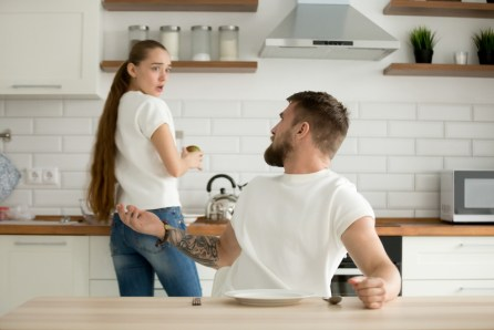 Young couple in conflict in kitchen. Image meant to portray couple who might benefit from learning couples communication skills in Massachusetts from a couples retreat in Massachusetts, Connecticut, or Maine.